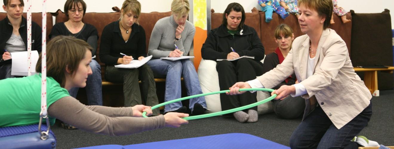Die Dozentin Birgit Pammé arbeitet mit einer Kursteilnehmerin auf der 4punktschaukel. Die anderen Teilnehmenden sehen im Hintergrund zu