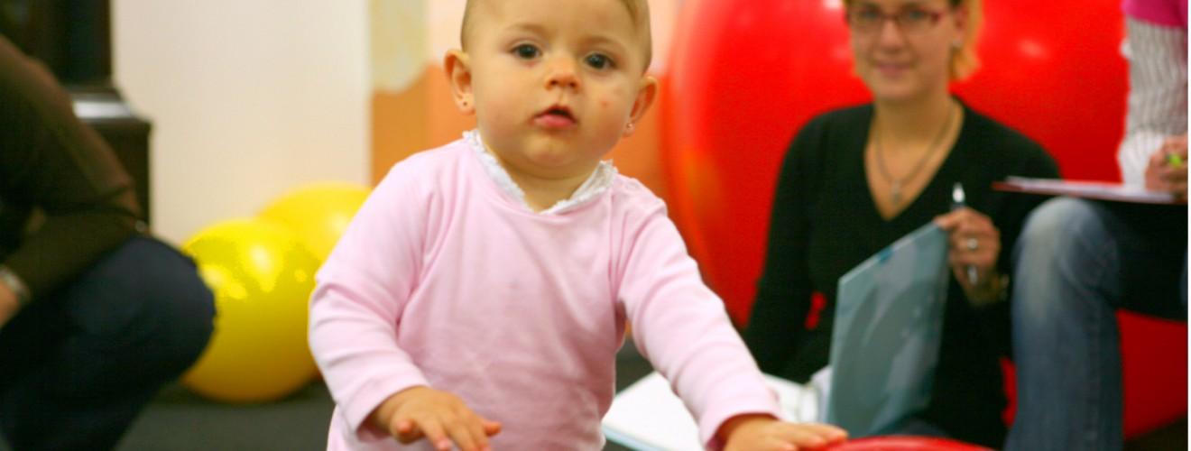 Das Kleinkind Louise spielt mit einem Therapieball und guckt herausfordernt in die Kamera