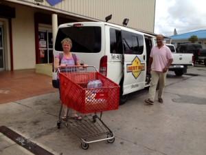 Birgit Pammé steht auf dem Parkplatz eines Supermarktes mit dem Einkaufswagen neben dem Shopping-Shuttle (ein Kleinbus)