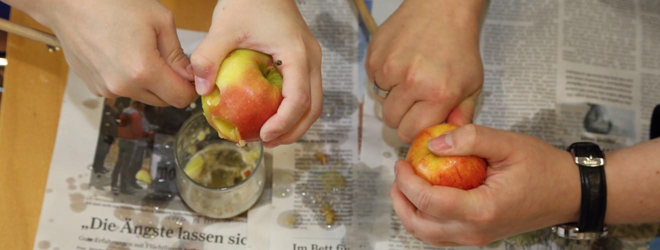 Teilnehmerinnen bei der praktischen Übung mit Holzstab und Apfel