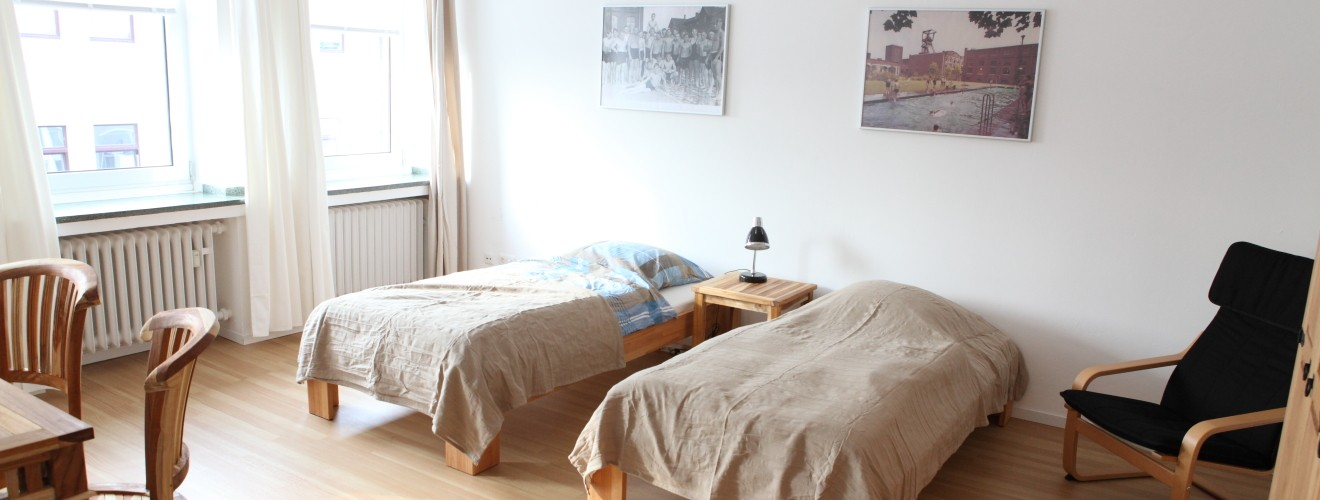 Rechtes Schlafzimmer des Apartments Pinguin, Blick auf zwei Betten, Loungesessel, Tisch mit Stühlen und helle Fenster