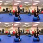 Teilnehmerinnen stehen auf dem Erdnussball und werden von Kurskolleginnen die auf dem Ball sitzen, an den Knieen stabilisiert. Die stehende Teilnehmerin wirft einen Ball quer durch den Raum zu einem weiteren Pärchen auf einem Erdnussball