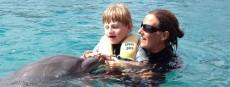 Delphintherapie mit Therapeutin und Kind im Wasser