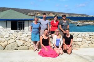 Gruppenbild mit Birgit Pammé mit den Teilnehmenden an der Hausinterne Fortbildung im CDTC vor einer Natursteinmauer mit dem Meer im Hintergrund
