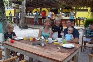 Kursteilnehmerin aus Brasilien mit ihrer Familie sitzen gemeinsam beim Essen am Tisch