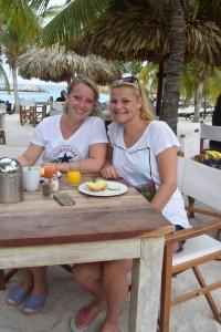 Zwei ehem. Kursteilnehmerinnen sitzen am Strand unter Palmen