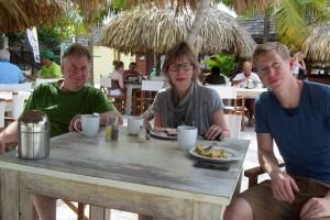 Teilnehmerin sitzt mit ihren Begleitern zum essen am Tisch unter Palmen und Sonnenschirm