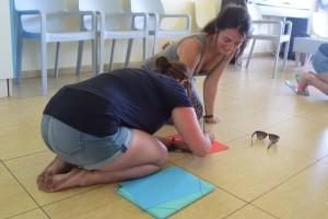 Zwei Kursteilehmerinnen knieen auf dem Boden bei der Gruppenarbeit