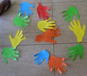 Ausgerissene bunte Papierhände von der Gruppenarbeit liegen auf dem Boden