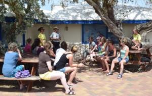Kursteilnehmerinnen sitzen draußen und lassen sich die Arbeit des CDTC vorstellen