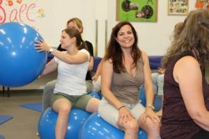 Teilnehmerinnen sitzen auf Bällen im Kreis und reichen einen Ball nach hinten weiter.