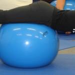 Teilnehmerin liegt mit dem Bauch auf dem Ball und und stützt sich mit den Armen ab.