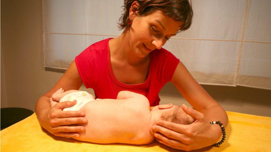 Die Dozenting Kathi Exner-Panne arbeitet mit einen Säugling auf einer Behandlungsbank