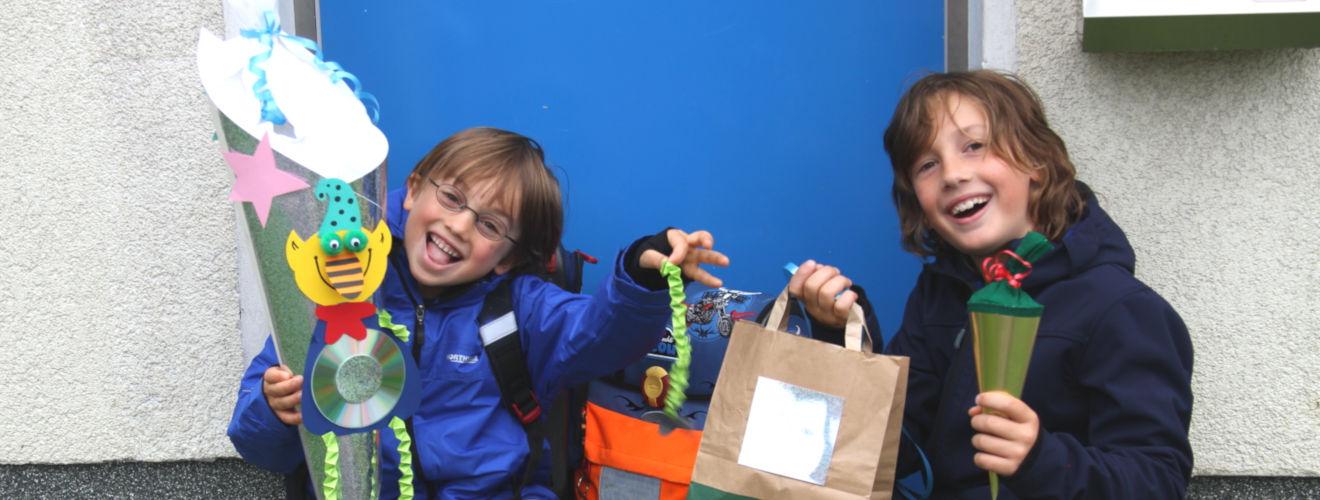 Moritz (re.) und Max (li.) sitzen vor der blauen Haustür mit Schultüten