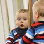 Kleinkind guckt in den Spiegel und beobachtet den Fotografen