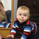Kleinkind guckkt in die Kamera und im Hintergrund ist seine Mutter im Spiegel zu sehen