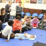 Kursteilneher, Dozentin und Mutter sitzen auf Matten im Kreis und beobachten einen