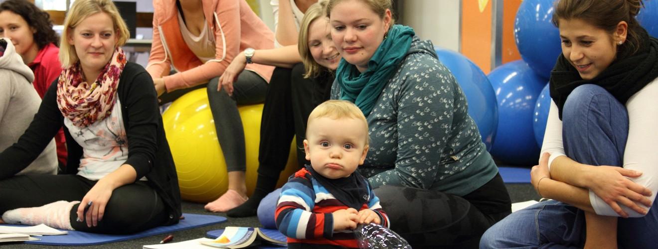 """Bobath-Pädiatrie-Kurs 2015-16: Thema """"Normale Entwicklung"""". Die Kursteilnehmer beobachten einen Kleinkind und einen Säugling. Auf diesem Bild sitzt ein Kleinkind mit einer Plastikflasche in der Hand vor den Teilnehmern"""