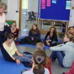 Kursteilnehmer erarbeiten unter Anleitung der Dozentin Birgit Pammé mit einer Decke aneinander gezielt Bewegungsübergänge des ersten Lebensjahres