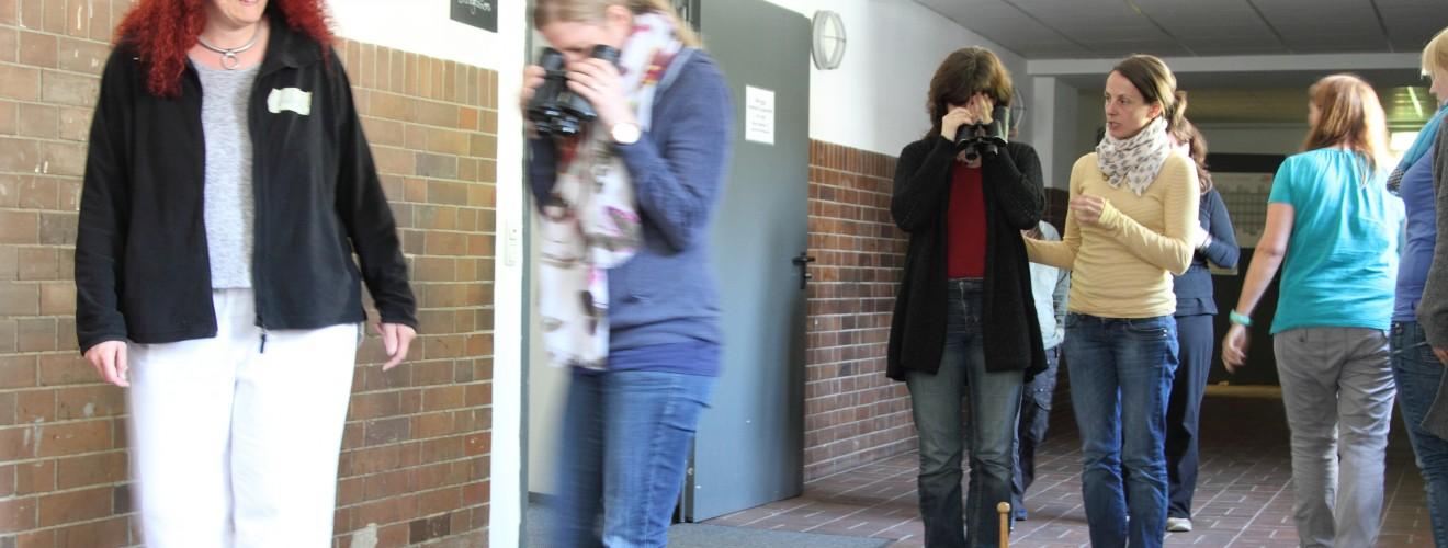 """SI 1 Einführungskurs April 2015. Teilnehmerinnen gehen mit einem """"falschherum"""" gehaltenen Fernglas über den Flur und die Außentreppe"""