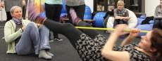 Eine Teilnehmerin spannt ein horizontales Seil und eine Weitere hangelt sich fußwärts am Seil entlang
